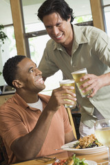 Two men toasting at restaurant
