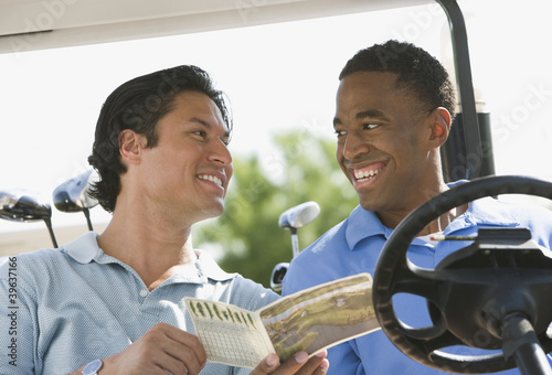 Two men smiling at each other in golf cart