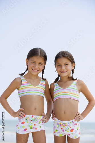 Hispanic sisters wearing matching bathing suits