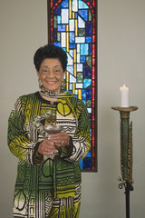 Senior African woman holding goblet in church