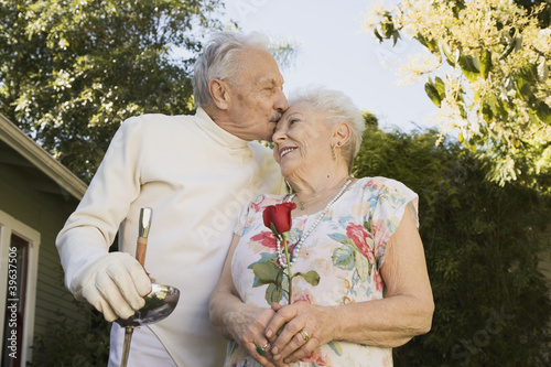Senior man in fencing gear kissing wife