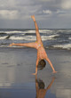 Woman doing cartwheel on beach