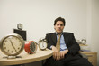 Hispanic businessman surrounded by clocks