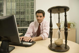 Hispanic businessman looking at hourglass on desk