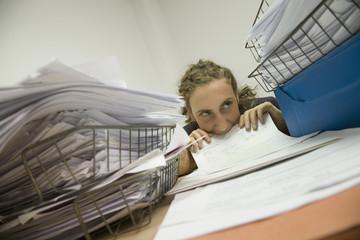 Hispanic businesswoman biting paperwork
