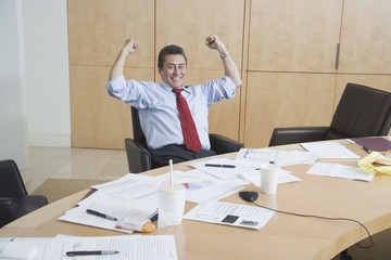 Hispanic businessman cheering at conference table