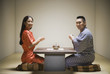 Asian couple kneeling having tea