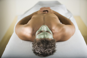 Man laying on spa table with facial treatment