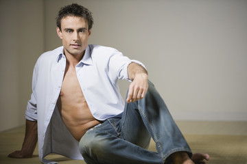 Man sitting on floor with shirt unbuttoned