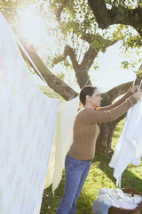 Hispanic woman hanging laundry on clothesline