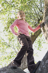Low angle view of Hispanic girl standing in tree