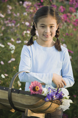 Asian girl holding basket of wildflowers