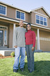 African couple posing in front of house