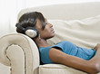 African woman laying of sofa listening to headphones