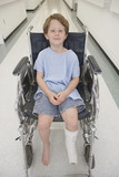 Boy with broken let sitting in wheelchair in hospital corridor