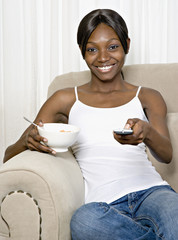African woman eating cereal and changing channel with remote control