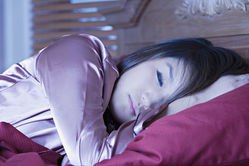 Young Asian woman sleeping in bed