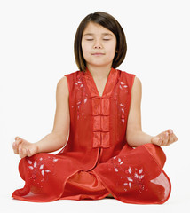 Studio shot of Asian girl in traditional dress meditating