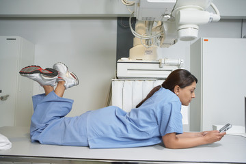 Indian female nurse laying on table using cell phone