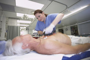 Female nurse defibrillating senior male patient