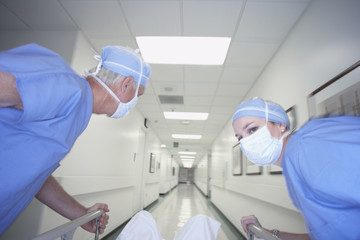 Male and female doctors wheeling gurney down corridor