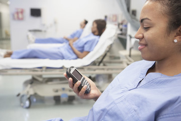 African female nurse using cell phone in hospital bed