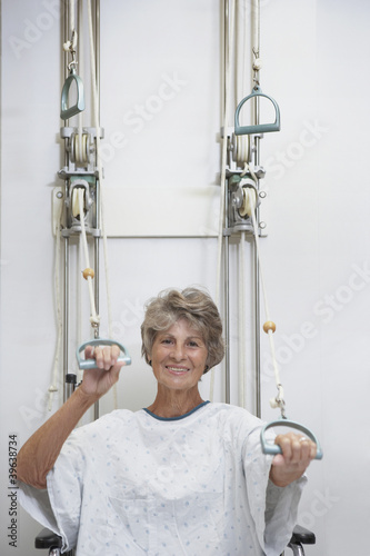 Senior female patient performing physical therapy in hospital gown