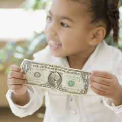 African girl holding dollar bill