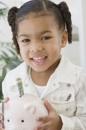 African girl holding piggy bank