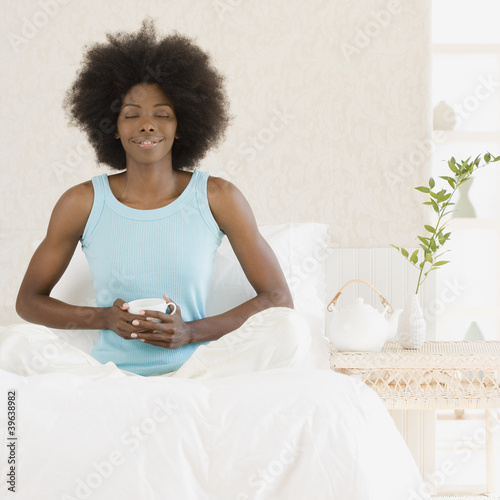 African woman relaxing on bed