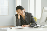 Asian businesswoman sitting at desk with head in hand