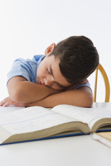 Hispanic boy napping on textbook