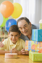 Hispanic grandfather and grandson hugging near birthday gifts
