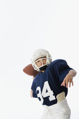 Studio shot of boy throwing football