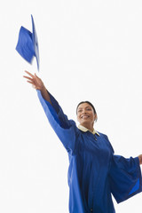 Studio shot of Indian woman throwing graduation cap in air