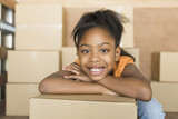 African girl leaning on moving boxes