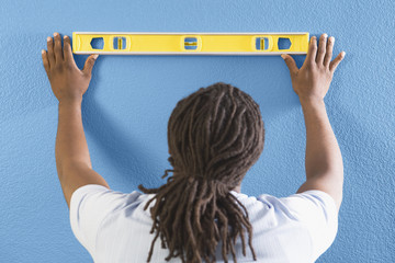 Rear view of African man using level on wall