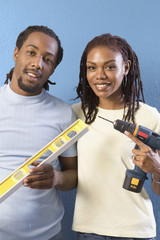 African couple with level and power drill