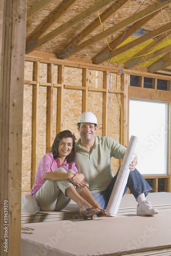 Couple with blueprints on construction site