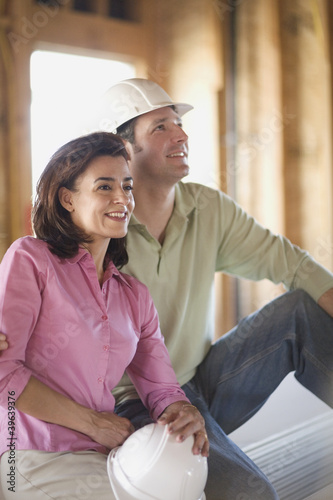 Couple with hard hats on construction site