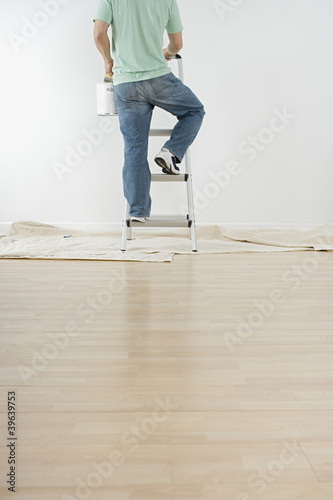 Hispanic man climbing ladder