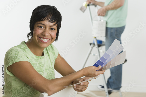 Portrait of Hispanic woman holding paint swatches