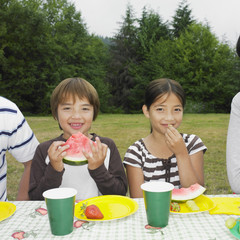 Mixed Race brother and sister eating watermelon