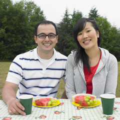 Portrait of Mixed Race couple at picnic table