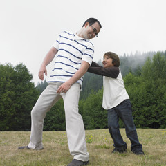 Mixed Race father and son playing at park