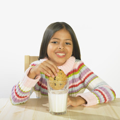 Hispanic girl eating milk and cookies