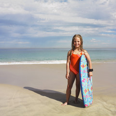 Portrait of girl holding boogie board at beach