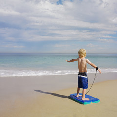 Boy standing on boogie board at beach