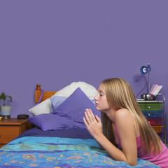 Teenaged girl praying in bedroom