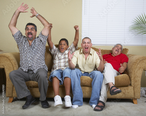 Multi-generational Hispanic male family members cheering on sofa